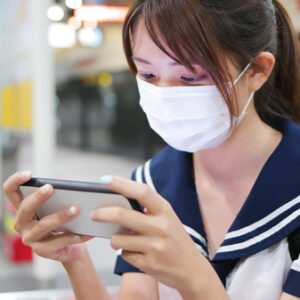 senior high school student girl use mobilephone when wait for mrt and wear face mask in the station